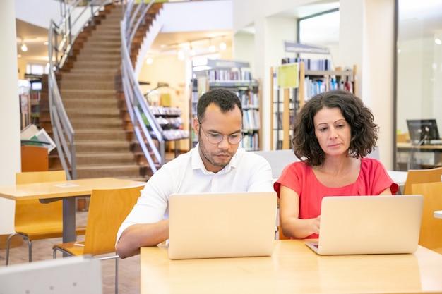 Equipe de dois estudantes adultos fazendo pesquisa