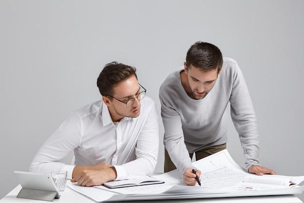 Equipe de dois jovens construtores europeus barbudos e elegantes verificando o plano de construção no interior de um escritório moderno