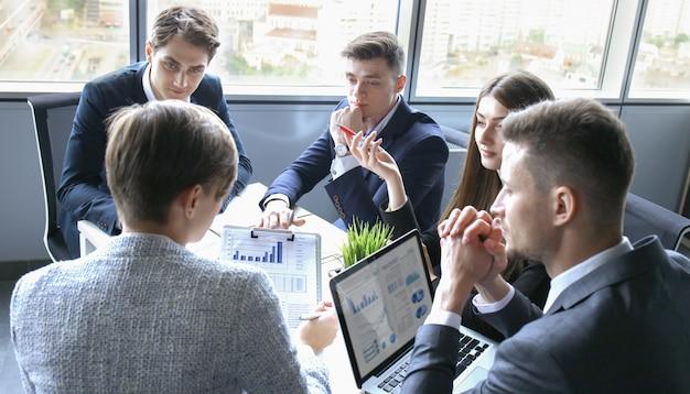 Equipe de empresários discutindo à mesa no escritório criativo.