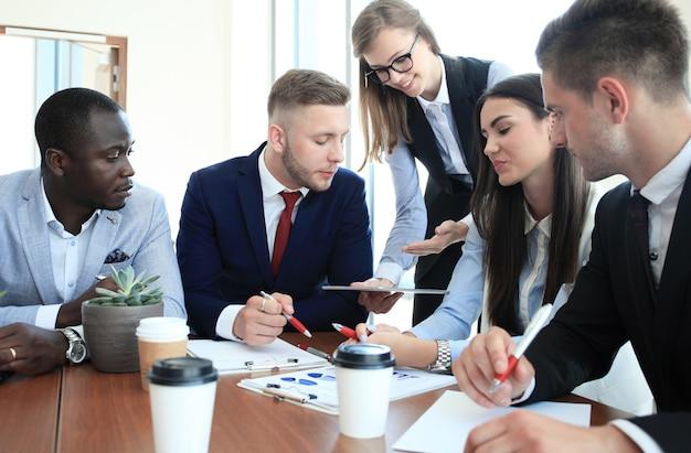 Equipe de empresários discutindo à mesa no escritório criativo