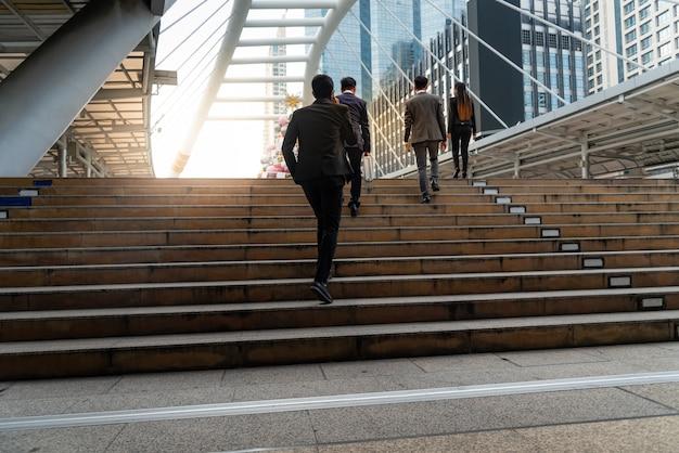 Equipe de empresários, grupo subindo as escadas no centro da cidade cheio de edifícios altos.