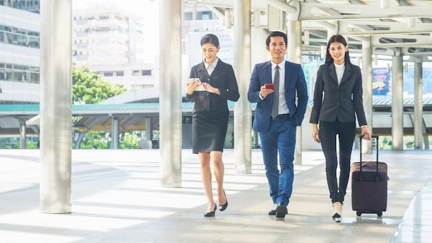 Equipe de empresários, homem e mulher inteligentes, caminham na hora do rush em uma passarela ao ar livre para pedestres e conversam com um tablet