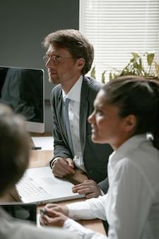 Equipe de empresários trabalham no escritório. foco seletivo em homem branco de óculos, olhando para