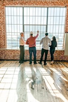 Equipe de engenharia ecológica discutindo perto das janelas de vidro