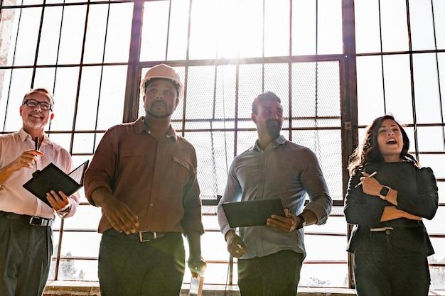 Equipe de engenharia ecologicamente correta em frente a uma janela de vidro