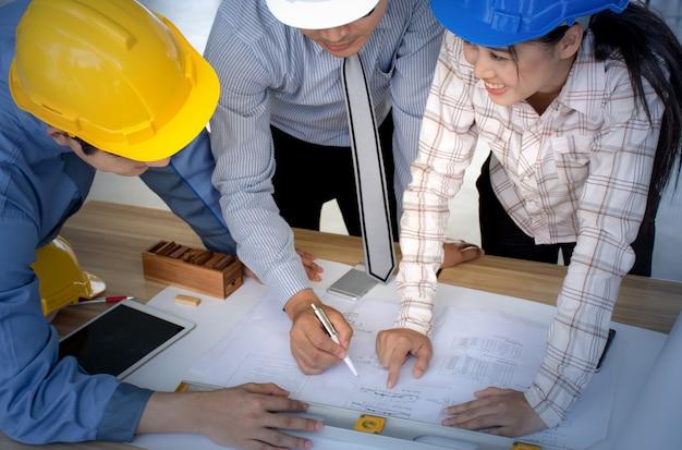 Equipe de engenheiro, equipe de arquiteto procurando planos de papel no canteiro de obras