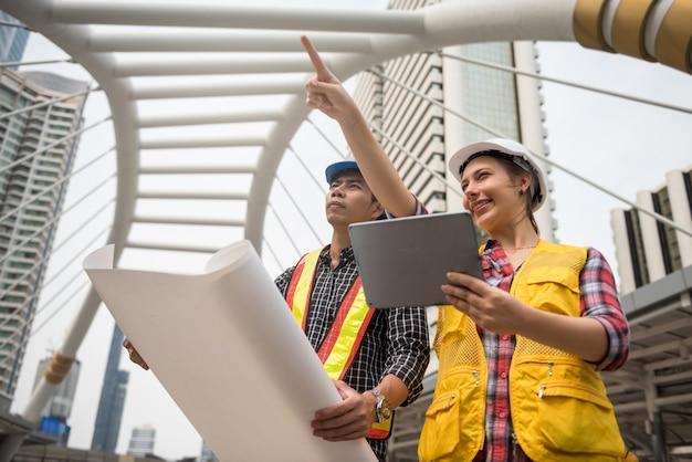 Equipe de engenheiro verificar o plano de construção no tablet