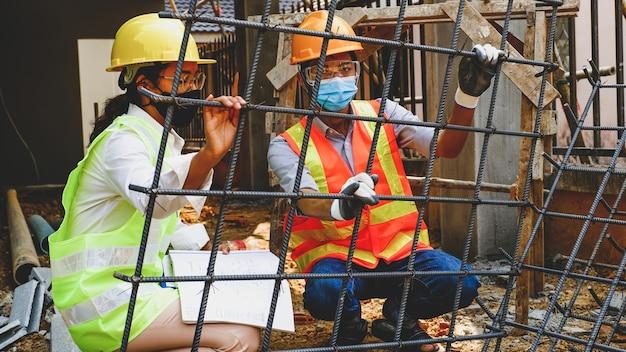 Equipe de engenheiros contratados reunindo-se com o projeto da indústria de segurança do trabalho, verificando o projeto da planta da casa e investigando o tamanho e a qualidade do aço usado no canteiro de obras de construção civil.