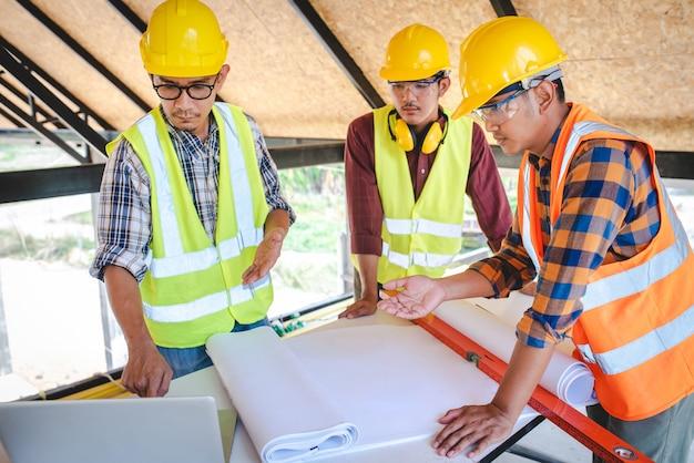 Equipe de engenheiros de construção e três arquitetos na reunião para projetar a construção e discutir o desenho da casa e o planejamento da construção na área de construção.
