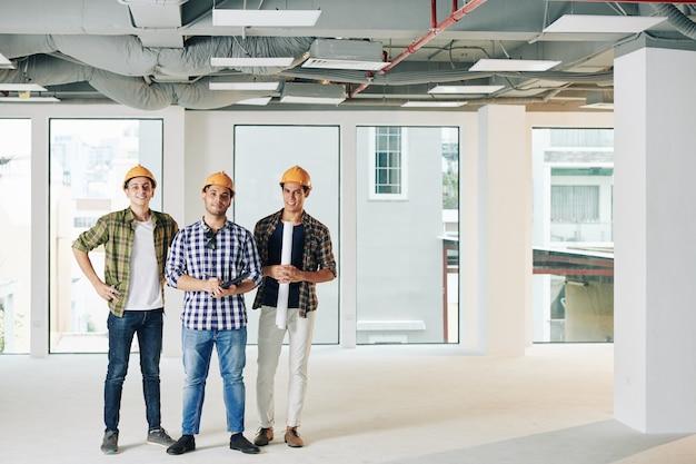 Equipe de engenheiros de construção sorridentes com projeto e tablet digital na casa em construção