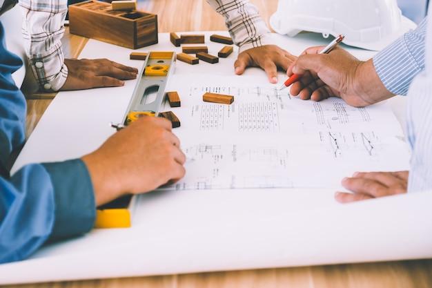 Equipe de engenheiros discutindo arquitetura plano esboço no local da construção.