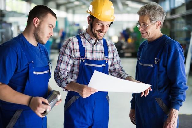Equipe de engenheiros discutindo na fábrica de metal