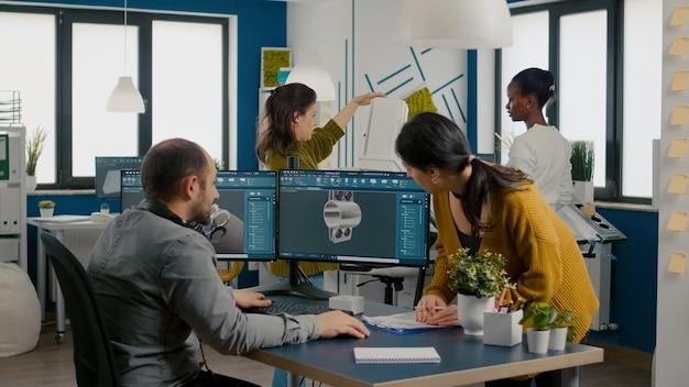 Equipe de engenheiros falando em frente ao pc com software cad