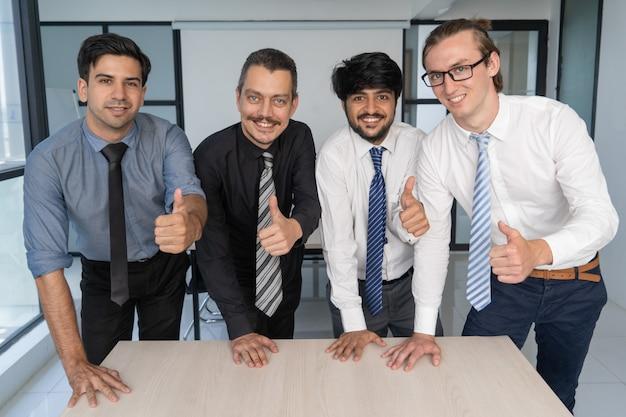 Equipe de especialistas em negócios posando com polegares para cima.