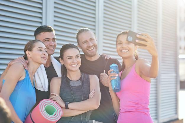 Equipe de esporte feliz tirando selfie na construção de fundo de parede