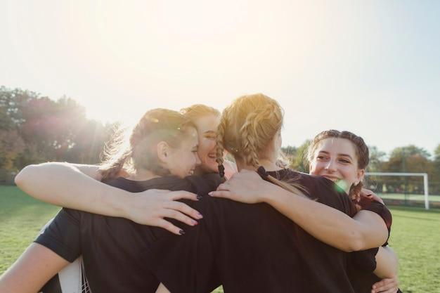 Equipe de esporte feminino bonito abraçando
