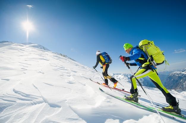 Equipe de esqui cross country casal de homens em direção ao cume da montanha