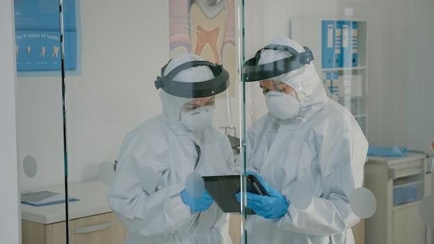 Equipe de estomatologia de dentistas segurando um tablet para exame de cuidados com os dentes