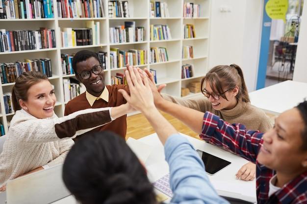 Equipe de estudantes cumprimentando na biblioteca