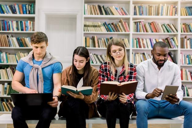 Equipe de estudantes multiétnicas, dois meninos e duas meninas, sentados juntos na faculdade ilbrary no espaço de grandes estantes de livros