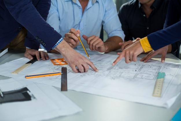 Equipe de executivos de negócios, discutindo a planta na reunião