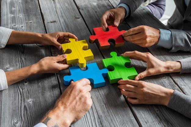 Equipe de executivos sentados ao redor da mesa de reunião e montando peças de quebra-cabeça de cores e conceito de idéias de cooperação