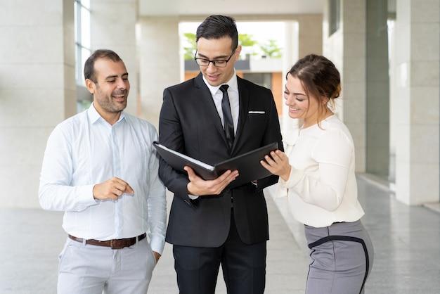 Equipe de feliz financistas lendo o relatório sobre o progresso da empresa Foto gratuita