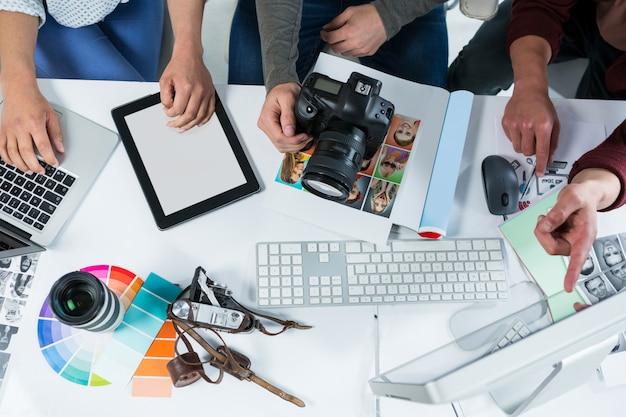 Equipe de fotógrafos trabalhando sobre o computador na mesa