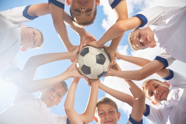 Equipe de futebol júnior feliz segurando uma bola
