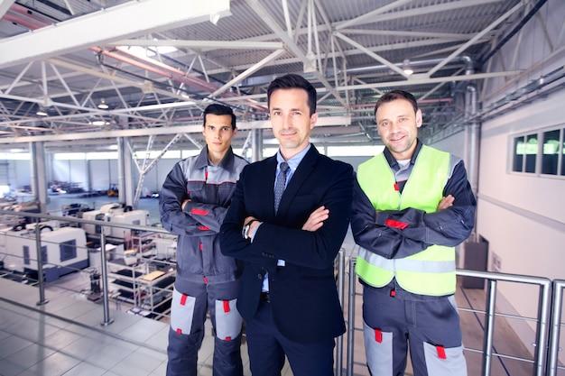 Equipe de gerente e dois trabalhadores na fábrica cnc