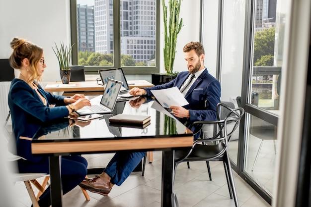 Equipe de gerentes analíticos trabalhando com gráficos de papel e laptops no escritório