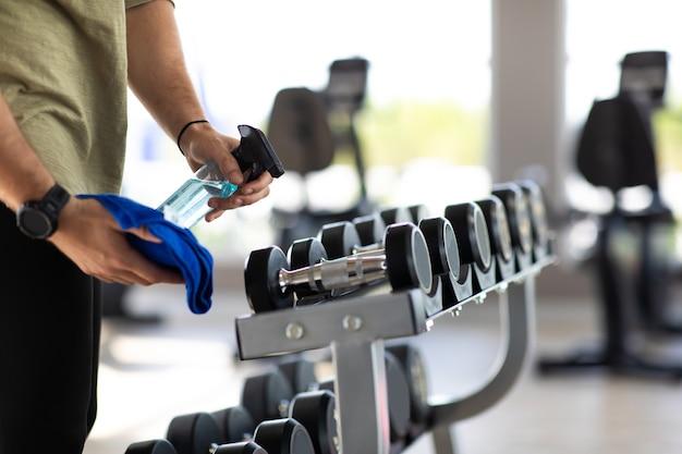 Equipe de ginástica limpando máquinas de exercícios com spray desinfetante de álcool na academia.