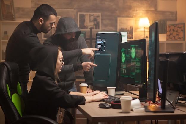 Equipe de hackers apontando na tela do computador e o terrorista cibernético feminino.