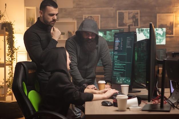 Equipe de hackers homens e mulheres criando um malware perigoso para atacar servidores corporativos.