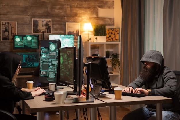 Equipe de hackers internacionais vestindo um moletom usando computadores de alto desempenho.