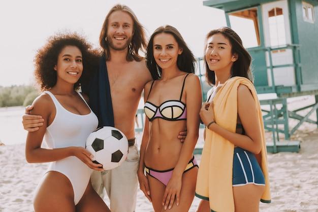 Equipe de hipster feliz homem e praia futebol meninas