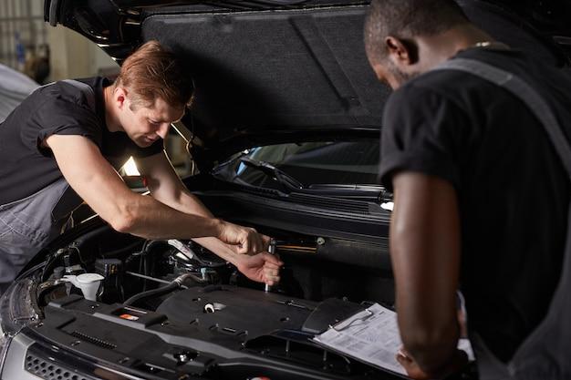 Equipe de homens africanos e caucasianos trabalhando juntos no serviço automotivo