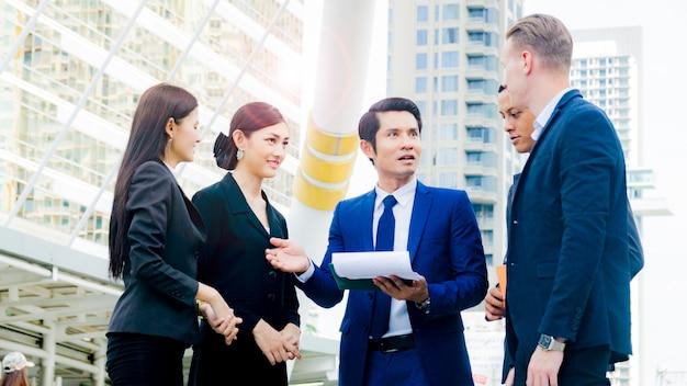 Equipe de homens e mulheres inteligentes de empresários falam e apresentam o trabalho do projeto com a papelada.