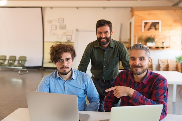 Equipe de inicialização bem sucedida feliz com laptops posando na sala de reuniões