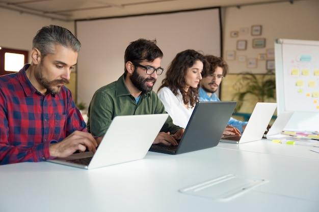 Equipe de inicialização colaborando no projeto, usando laptops