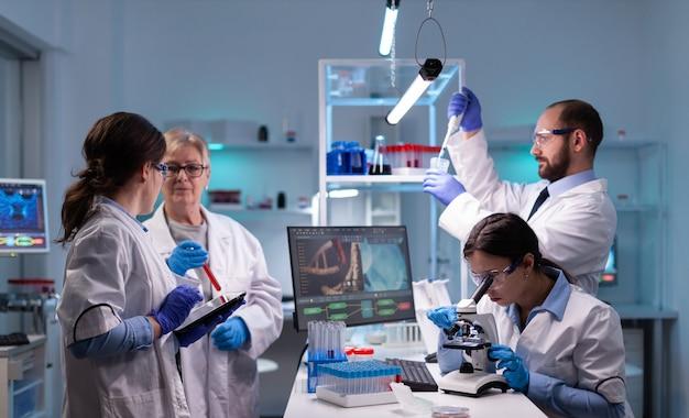 Equipe de investigadores científicos conduzindo experimentos em laboratório usando microscópio e micropipeta