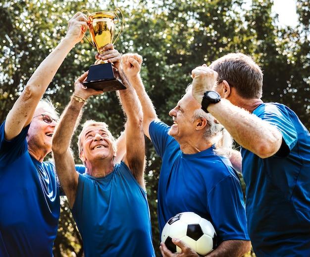 Equipe de jogadores de futebol maduros, vencendo a taça