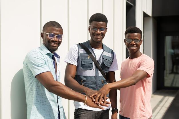 Equipe de jovens africanos de mãos dadas