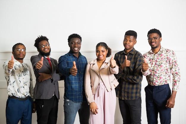 Equipe de jovens africanos dentro de casa com gesto de mão