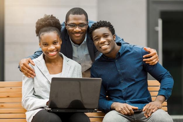 Equipe de jovens africanos homens e mulheres com laptop