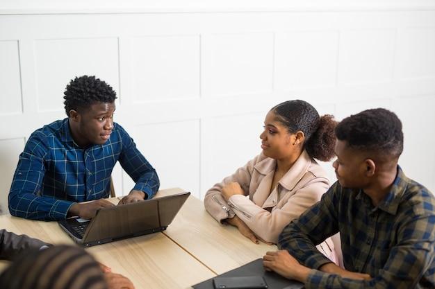 Equipe de jovens africanos trabalhando no escritório à mesa com laptop