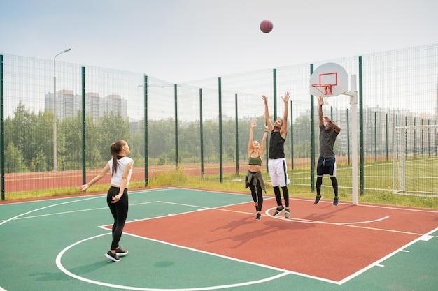 Equipe de jovens amigos interculturais ou estudantes se exercitando na quadra de basquete em um dia de verão