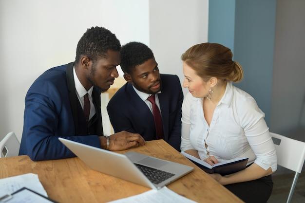 Equipe de jovens bonitos no escritório à mesa com um laptop