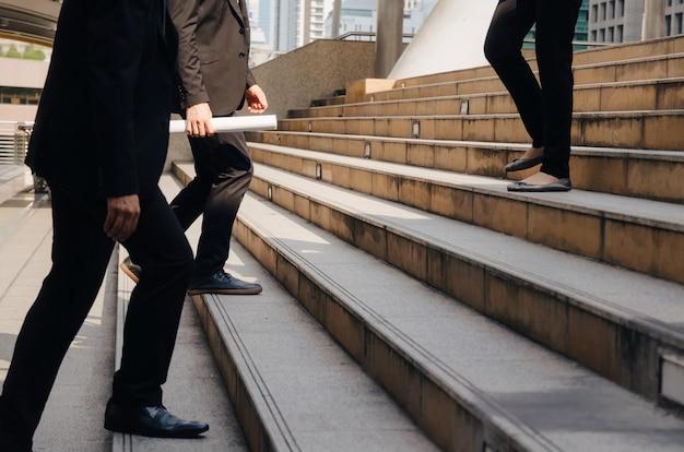 Equipe de jovens empresários andando rápido subir e descer escadas indo para o tempo de trabalho