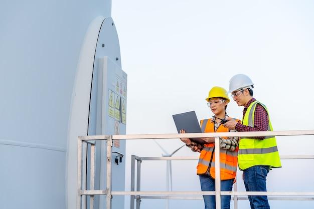 Equipe de jovens engenheiros trabalhando com um computador laptop contra uma fazenda de turbinas eólicas